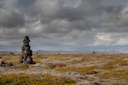 sky and moss surround cairn in Iceland 写真素材