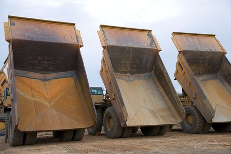 Three large dump trucks as seen from behind