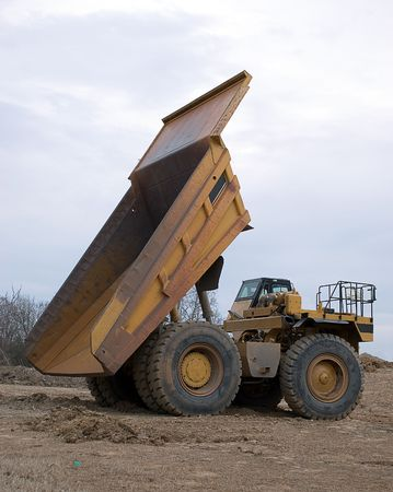 Large yellowdumptruck with bed elevated Imagens