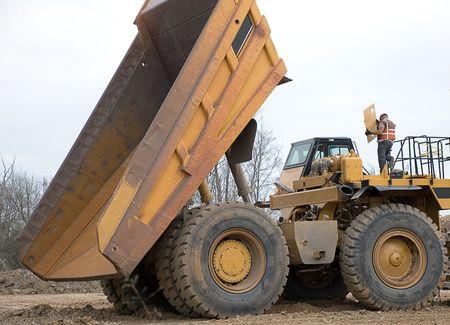 Large yellowdumptruck with bed elevated and mechanic on top