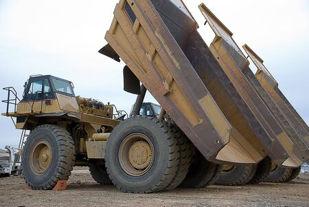 Large yellow dump truck with bed raised Imagens