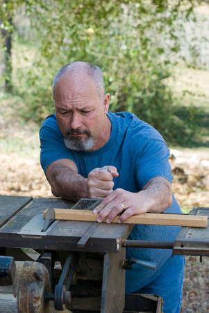 Man using table saw to cut board