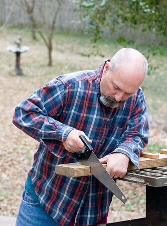 Man using small hand saw to cut board