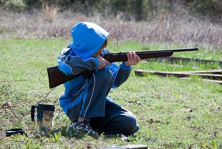Boy kneeling while shooting rifle