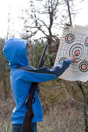 Boy checking his target while holding his rifle