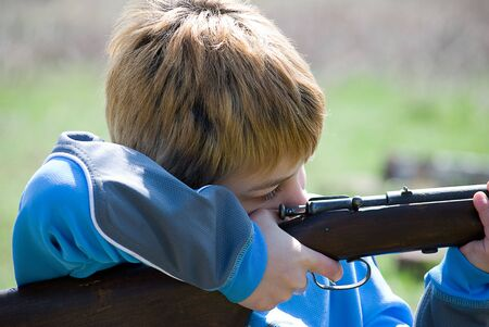 Colse up of boy pulling trigger on rifle
