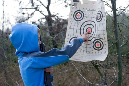 Young boy pointing out bullseye shot while holding rifle