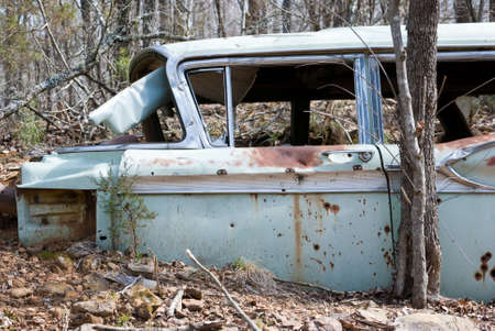 Old rusty abandoned car with bullet holes in it