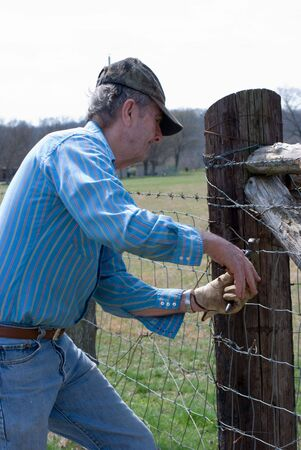 Man repairing fence with fence pliers