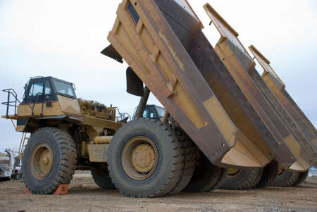 Large yellow dump trucks lined up with beds elevated Imagens