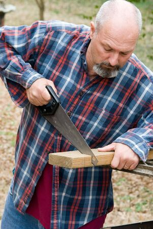 Man cutting board with small hand saw