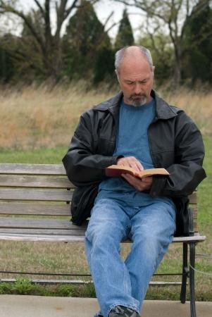 Man zittend op een bankje, lezen zijn bijbel Stockfoto