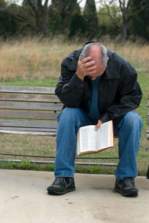 Sad looking man sitting on bench while holding his bible