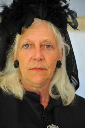 18th: Elderly woman wearing black clothing to indicate mourning. Clothing typical of late 18th century Stock Photo