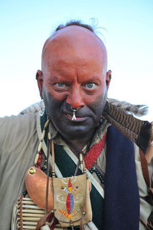 cree: Angry looking warrior dressed in war paint and wearing jewelry