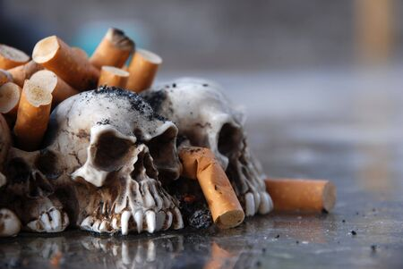 Ashtray made of tiny skulls, filled with cigarette butts and ashes Stock Photo