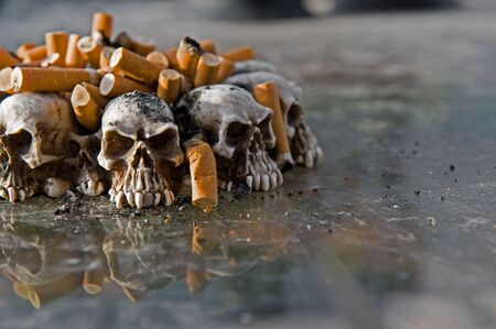 Ashtray of skulls filled with cigarette butts and ashes
