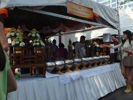 Wat Pathum Wanaram, Bangkok - March 7, 2012 - Makha Bucha Day, a girl donate to build her birthday diurnal Buddha icon. Stock Photo - 12676642
