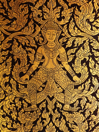 Thai golden painting art on the door of ancient tripitaka building. Look like some angel (deva) stand to guard this door. photo