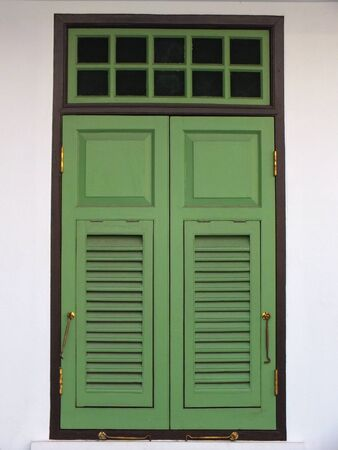 louver boards: An old green window panels on it frame.