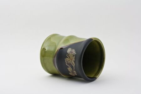 toppled: A toppled green cup in a shape of a bamboo