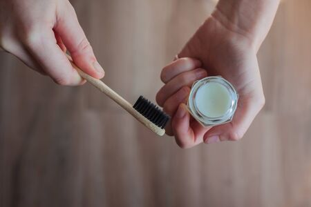 Young woman holding a bamboo toothbrush with one hand and zero waste toothpaste with the other