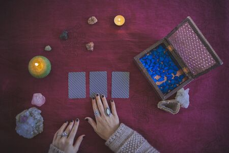Young woman placing three tarot cards to predict the future, with a mystic background of candles, stones and crystals