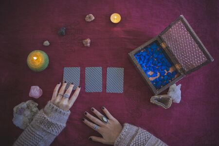 Young woman taking the first of three tarot cards to predict the future, with a mystical background of candles, stones and crystals
