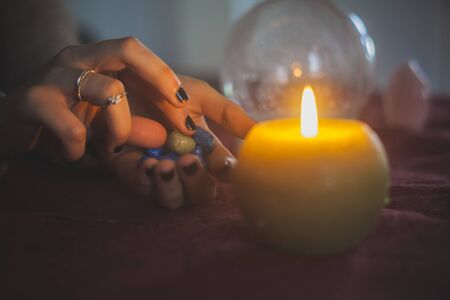 Young woman catching a stone from the ones in her hand with a mystical background of candles and crystal ball