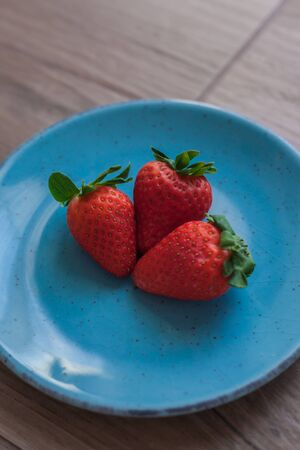 Strawberries close-up on a blue plate with rustic wooden background
