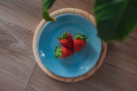 Strawberries on a blue plate and a wooden tray with leaves