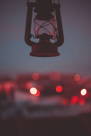 Red oil lamp with a rustic city background at dusk with phantom blue sky