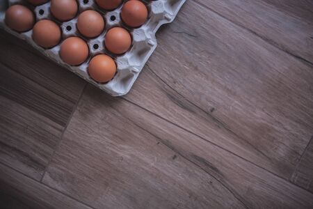 Rustic background of an egg carton in a corner on a wooden board