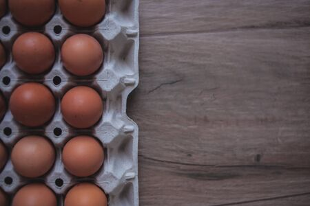 Rustic background of an egg carton on a wooden board