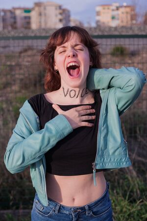 """Strong woman shrieking with the word """"voice"""" painted while holding her neck"""