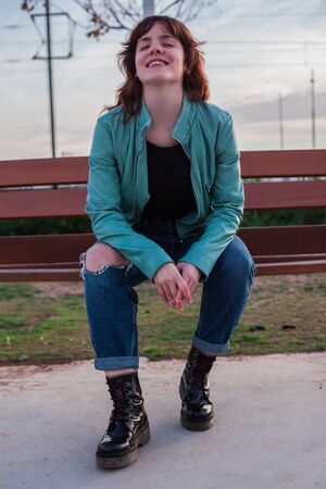 Young caucasian woman sitting on the bench in the park with a mint green jacket while smiling