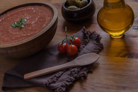 Bowl of Andalusian gazpacho with peppermint leaves with a rustic wooden spoon background, a cherry tomato, oil and olives