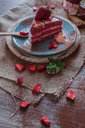 Red Velvet cake on a blue plate with strawberries and pure cocoa with a rustic background with flowers and cloth napkins