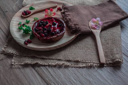 Cheesecake with blueberry and raspberry jam on a blue plate with mint, a wooden spoon, flowers and a wooden spoon
