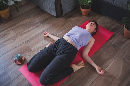 Young and attractive girl doing yoga (reclining hero pose)