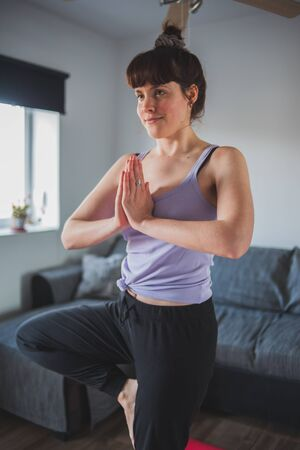 Young and attractive girl doing the yoga tree pose at home Фото со стока