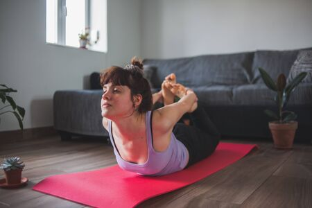 Young and attractive girl doing yoga (bow pose)