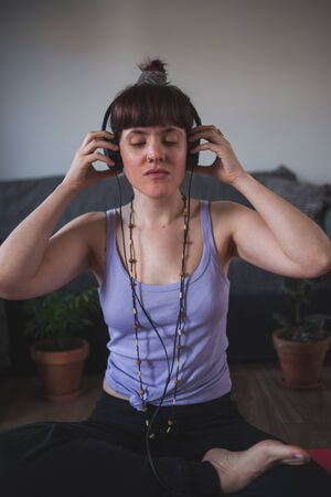Attractive young girl putting on headphones to do yoga at home Фото со стока