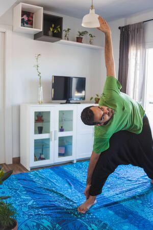 Young boy doing yoga at home. Trikonasana pose Фото со стока