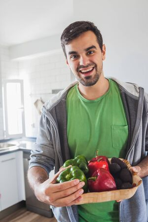 Man picking up a basket of green and red peppers and avocados Stock Photo
