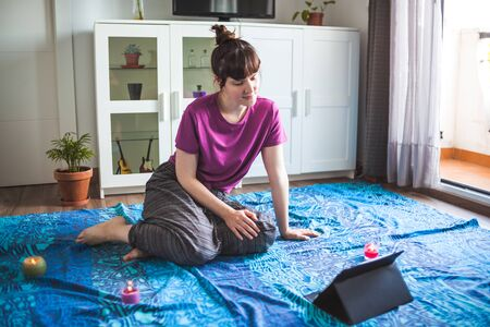 Young girl watching a meditation guided by her tablet in her apartment