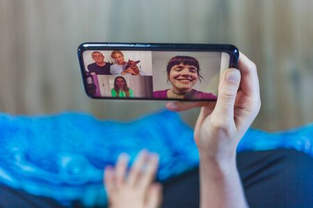 Close-up of a cellphone with a family video call on screen. Parents talking to their kids on video call.