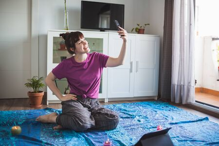 Young and attractive girl taking a selfie before starting to meditate in her apartment