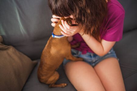 Attractive Young Woman Petting a Mini Pinscher Dog