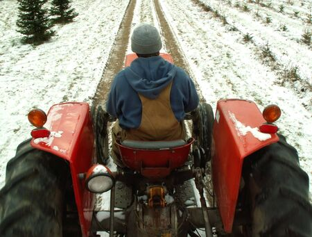 man driving a tractor in the winter